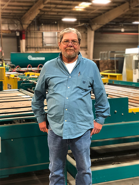 Man standing in custom sheet metal facility